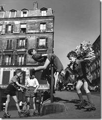Les enfants jouent dans la rue en patins à roulettes - 1950 © Ateliers Robert Doisneau